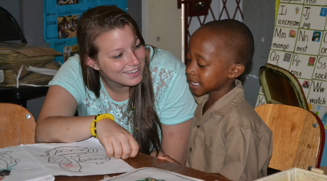 A volunteer goes through an English exercise during childcare volunteering in Jamaica for groups.